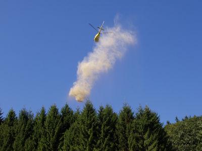 Ein Hubschrauber wirft gemahlener Kalkstein über Waldflächen des Ortenaukreises ab. Foto: LRA